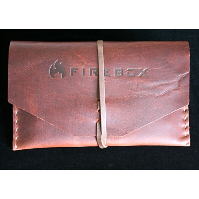 Firebox 5 inch camp stove in a brown leather case with a leather strap holding it together on a black velvet surface.