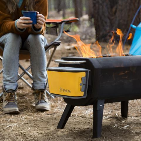 Person enjoying a camp mug beverage, while calmly watching the flames of the BioLite FirePit, out in the wilderness within the trees.