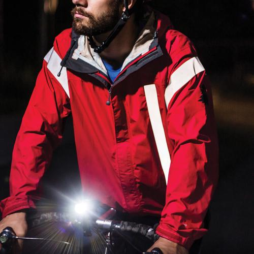 Man cyclist biking at night with a bike lamp and red jacket with taped tenacious reflective gear aid tape for extra night time visibility.