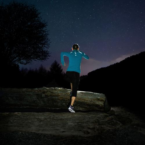 Woman jogging at night with a strips of Gear Aid's Tenacious Reflective Tape on her back.