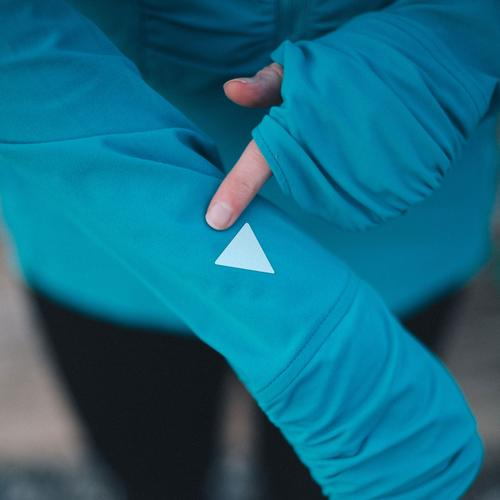 A triangular cut out of Gear Aid Reflective Tape on a cardinal blue zip up sweater sleeve.