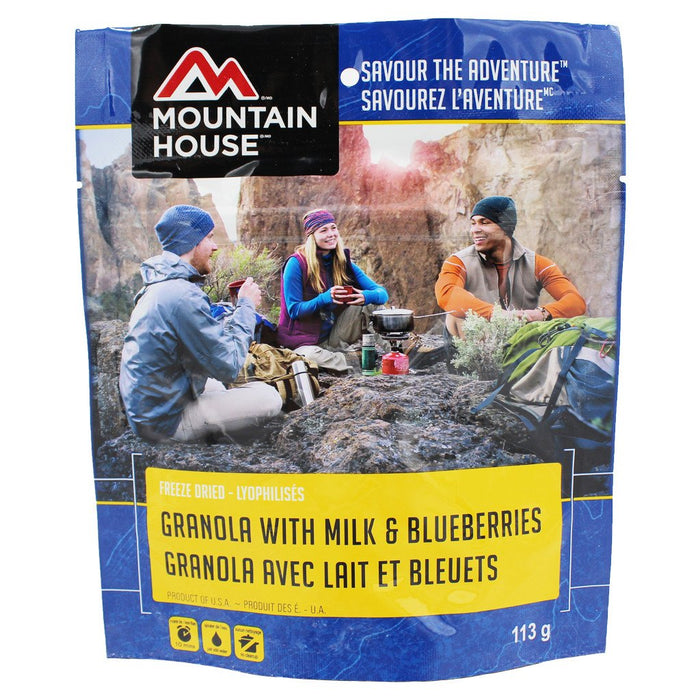 Mountain House Granola with Milk and Blueberries vacuum sealed package. Three trail hikers sit in a circle enjoying the snack in the morning. Light rays from the sun come through a rock face over their heads.