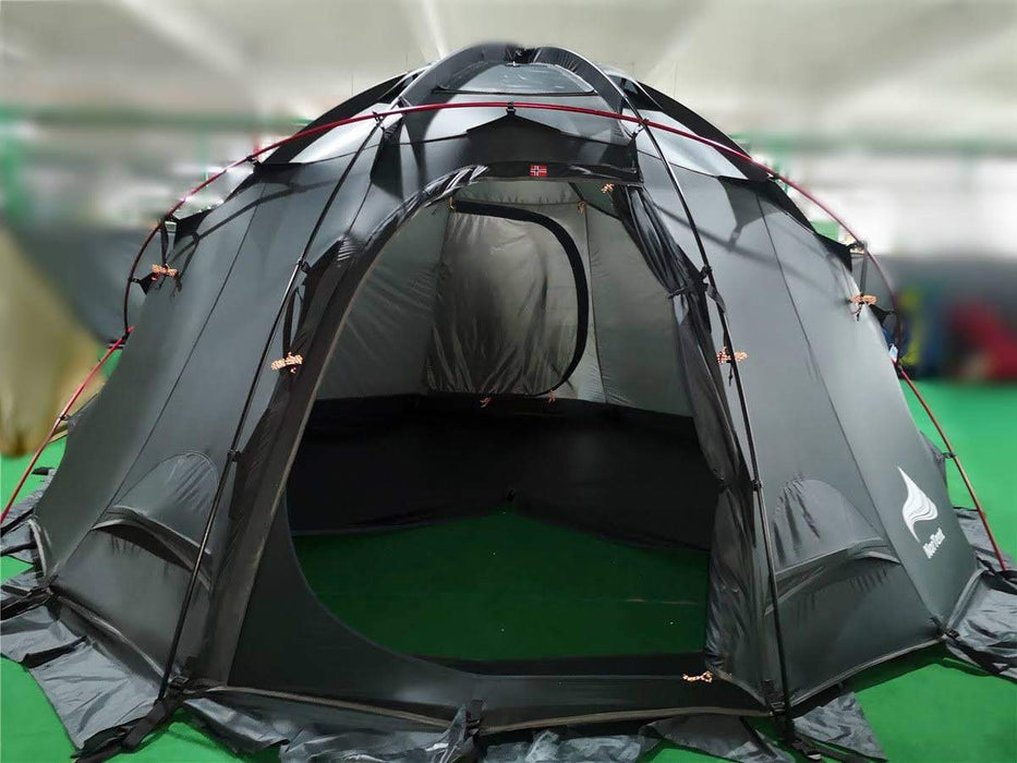 The completed construction of the NorTent Gamme 4 person tent in black with red tent poles. The entry was is open exposing the spacious inner tent on green astro turf.