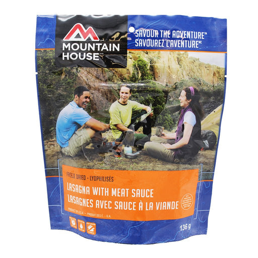 Mountain House Product package of Lasagna with Meat Sauce. There is an image of 3 people sitting around a gas powered camp stove in a canyon valley heating up and preparing the freeze dried food meal.