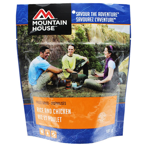 Mountain House Rice and Chicken Freeze Dried Food Package with three people enjoying the meal camping in a canyon valley.
