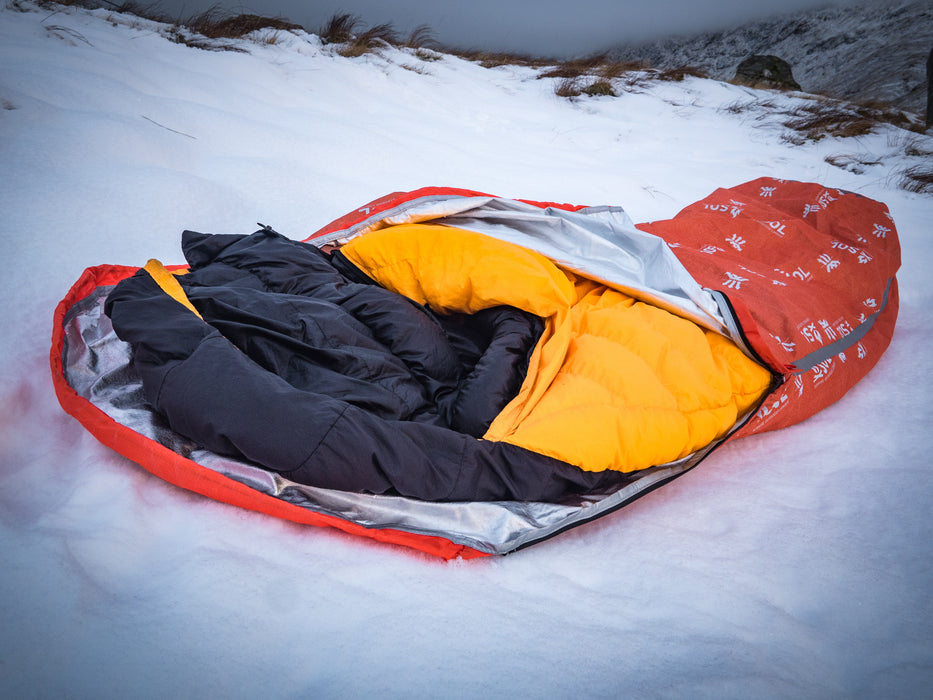 A orange and black sleeping bag stuffed into the Escape Pro Bivvy outdoors on a snowy hillside.