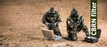 Two men in full Army Camo hazmat suits wearing gasmasks equipped with Mira NBC-77 40mm Thread filters in a desert area with two pelican cases with radiation meters and testing tubes. The description 'CBRN Filter' is shown in a green banner.