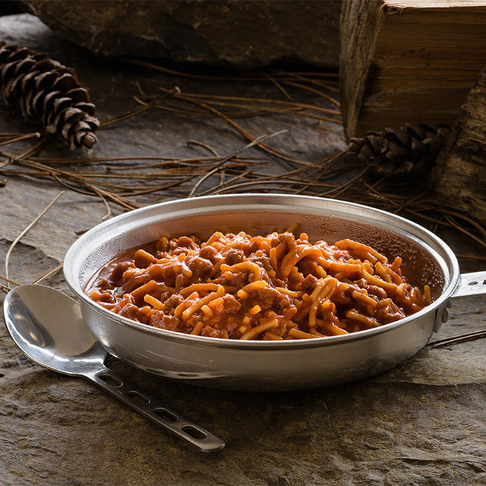 Stainless steel camping pot full of prepared Spaghetti and meat sauce freeze dried food. Surrounding the pot are pine cones and pieces of firewood.