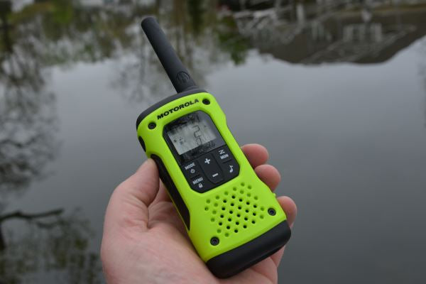 A person holding a T600 Two way Radio in one hand. The radio is a lime green with black accents and buttons. In the background is a lake with a reflection of a house in it.