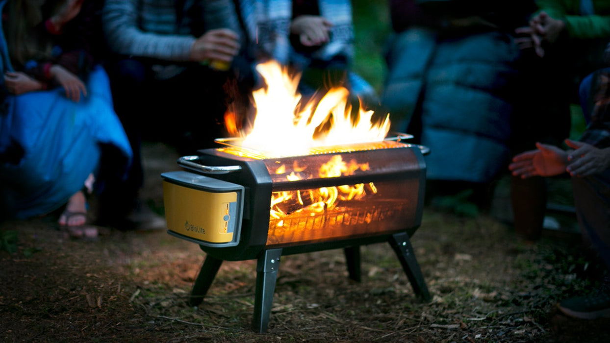 6 people camping with their hands out warming up on a cool summers night with the BioLite Firepit Smokeless Natural Fuel Pit.