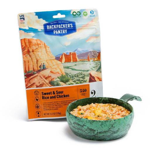 Front cover of Backpackers Pantry sweet and sour chicken with rice and vegetables freeze dried food package. Alongside is a fresh bowl of the prepared product in a camping pot with handle to heat over the fire.