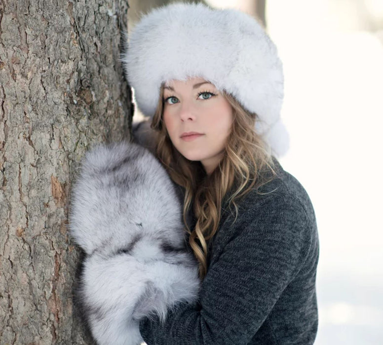Woman wearing the Blue Fox Fur Mitts with a Blue Fox Fur hat up against a tree in the outdoors with snow in the background.
