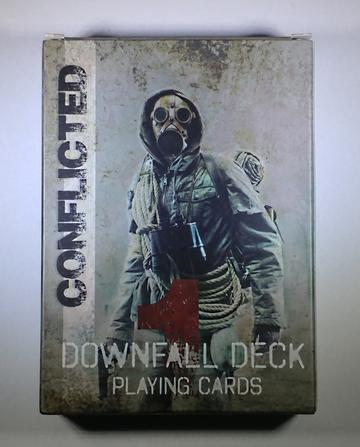 Conflicted Deck 1: The Downfall playing cards. A person wearing a forest green jacket a with gas mask on, binoculars around the neck and rope around wrapped the body poses on the front of the card deck..