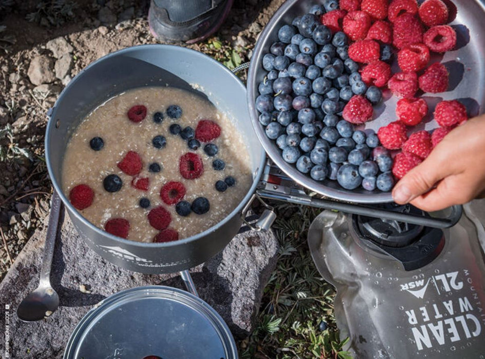 A person holding a titanium bowl of fresh blueberries and raspberries putting them into a titanium pot of oatmeal. A 2L rugged water bag from MSR is shown beside the bowl and everything is on a rocky covered ground.