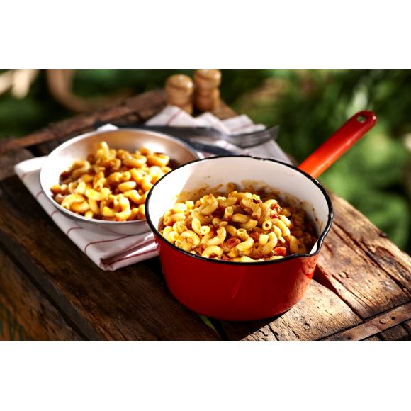A red camping cooking pot full of Happy Yak's Mom's Tomatoe and Cheese Macaroni, with a white bowl of the food laid on a wood crate in the outdoors.