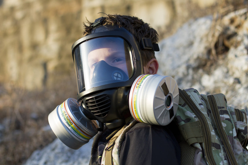 A man wearing the CM-6M TACTICAL GAS MASK with two repirator filters showing. On his is back is a army camouflaged backpack and a cliffside shows in the background.