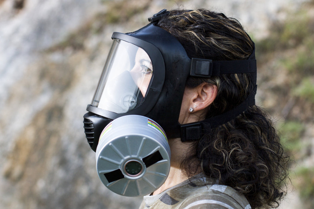 A woman with long brunette hair wearing the CM-6M TACTICAL GAS MASK with a large repirator filter shown. In the background is a cliffside and the woman is staring out in the distance.
