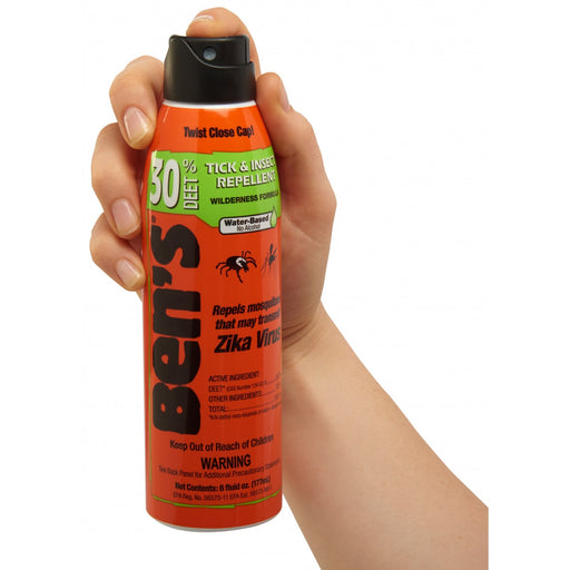 Hand holding Ben's® 30 Tick & Insect Repellent 6oz Eco-Spray canister. Descriptions of 'Tick and Insect Repellent' 'Wilderness Formula' and 'Water-Based, no Alcohol.' 177ml Orange canister with black cap.
