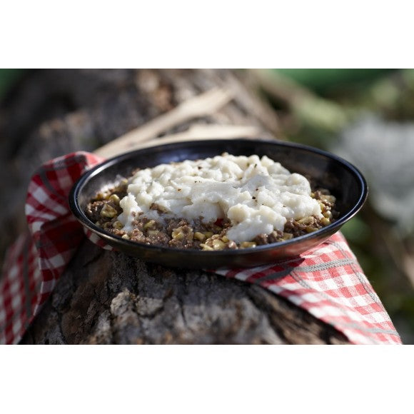 A bowl of prepared freeze dried Shepherds Pie on a red and white plaid coloured napkin resting on a tree log.