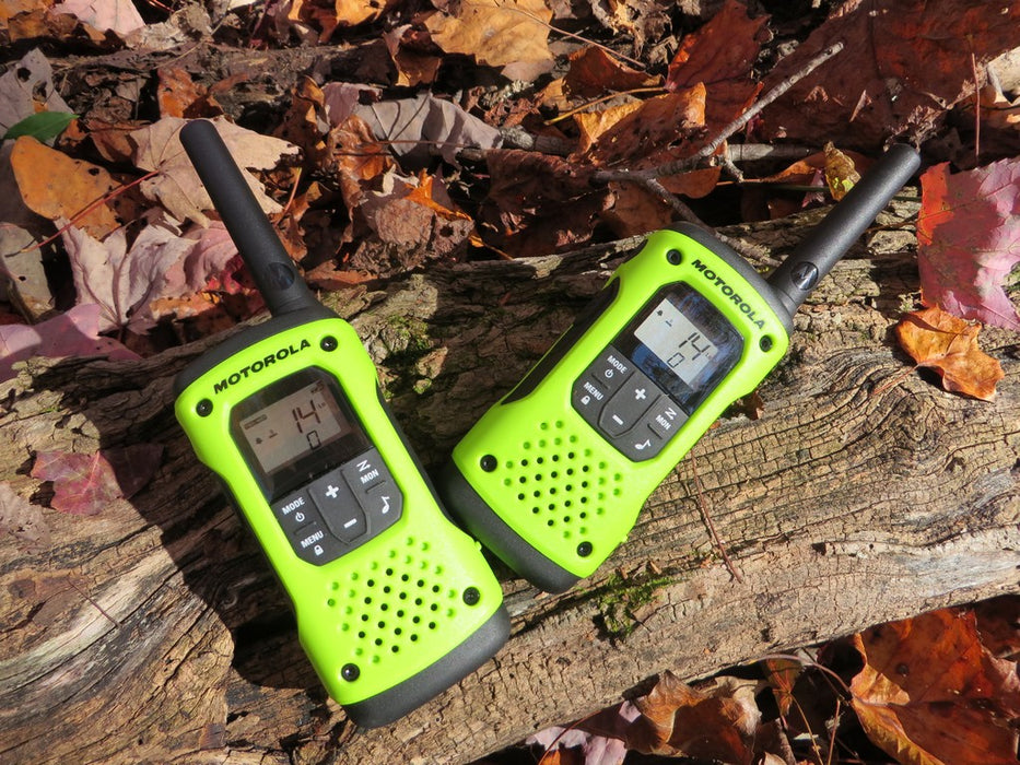 Two lime green and black Talkabout T600 Radios on a tree log in the fall. Leaves populate the surrounding area.