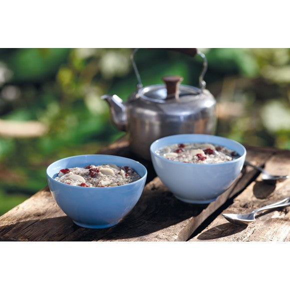 2 Pale Blue bowls of Happy Yak Chia with Almonds and Cranberry preppared Freeze Dried Food. The bowls are on a picnic table beside a kettle of hot water that was used to prepare the food.