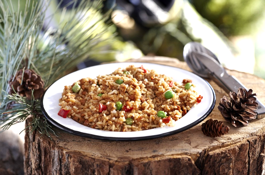 Happy Yak Express Teriyaki Rice (Soy, Peas, Sesame Seeds, Teriyaki sauce, and Red Bell Pepper). A plate of the Teriyaki Rice is shown laying on a tree stump beside a pine cone and camping utensils..