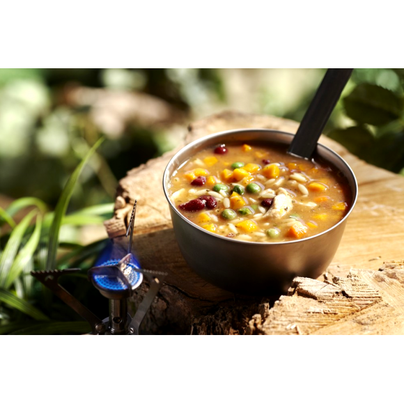 A camping bowl of Happy Yak Chicken Orzo Freeze Dried Soup is shown heated up by a camp stove torch on a tree stump outdoors.