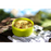A lime green bowl of the boiled and mixed freeze dried Happy Yak Coconut Thai Soup with a napkin and camping spoon on top of a tree log.