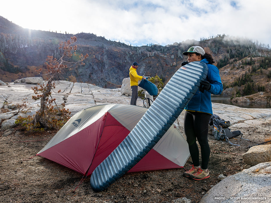 A person blowing air into a Thermarest Neoair mattress beside a red and grey coloured tent. The person is wearing running tights and a blue jacket. A person wearing a yellow jacket is unpacking their gear in the background. A hillside with scattered spruce trees and clouds is shown.