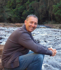 Photo of Greg Newson sitting by a river smiling at the camera