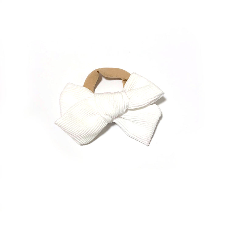 White corduroy bow headband, suitable for babies, on a nylon band