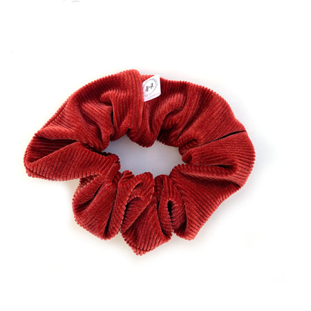 A deluxe velvet scrunchie in a warm Rust tone.