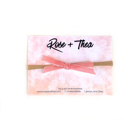 Soft pink velvet bow on a stretchy nylon headband