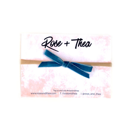 Blue velvet bow on one size fits all stretchy nylon headband by Rose and Thea
