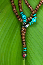 Brown wooden necklace with turquoise blue accents and multi colored pendant.