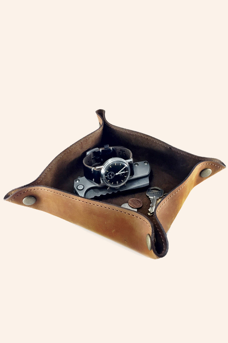 Handcrafted leather travel valet in brown. Assembled can hold small items such as watch, jewelry, keys, and coins.