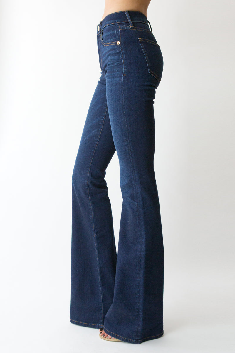 "Side View of Midheaven's Mid-Rise Indigo Flare  ITEM RUNS SMALL, CONSIDER SIZING UP   Details: Model is 6' and is wearing 4"" heels. Rise: 9"" Inseam: 38"" Leg Opening: 21"" Fabric contents: 98% Cotton - 2% Elastane"