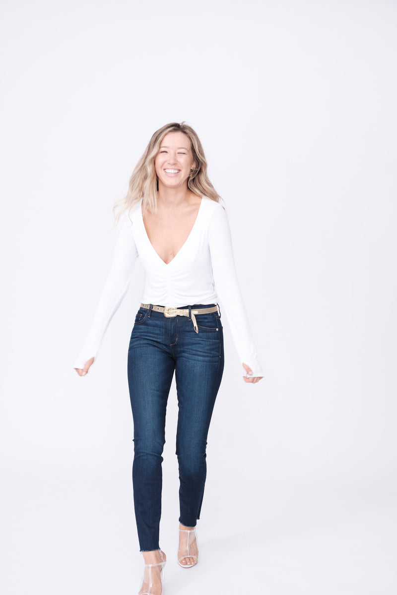 "Front View of Midheaven's Mid-Rise Raw Hem Skinny   ITEM RUNS SMALL, CONSIDER SIZING UP   Details: Model is 5'7"" and is wearing 4"" heels. Rise: 9"" Inseam: 28"" Leg Opening: 10.5"" Fabric contents: 98%Cotton - 2%Elastane"