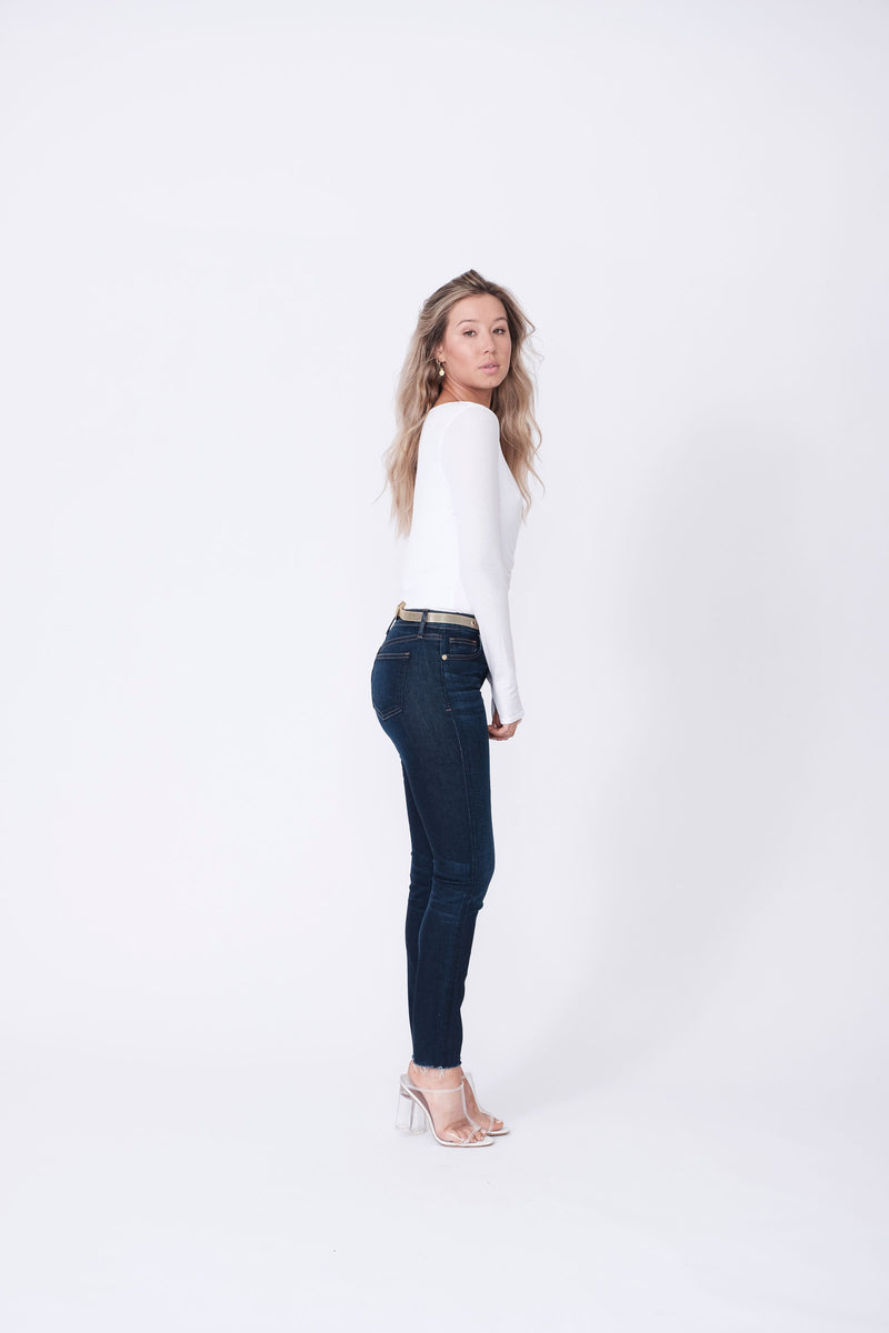 "Side View of Midheaven's Mid-Rise Raw Hem Skinny   ITEM RUNS SMALL, CONSIDER SIZING UP   Details: Model is 5'7"" and is wearing 4"" heels. Rise: 9"" Inseam: 28"" Leg Opening: 10.5"" Fabric contents: 98%Cotton - 2%Elastane"