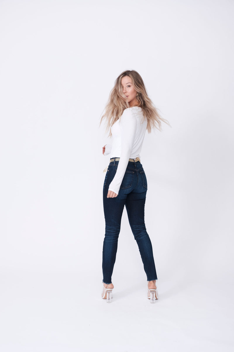 "Back View of Midheaven's Mid-Rise Raw Hem Skinny   ITEM RUNS SMALL, CONSIDER SIZING UP   Details: Model is 5'7"" and is wearing 4"" heels. Rise: 9"" Inseam: 28"" Leg Opening: 10.5"" Fabric contents: 98%Cotton - 2%Elastane"