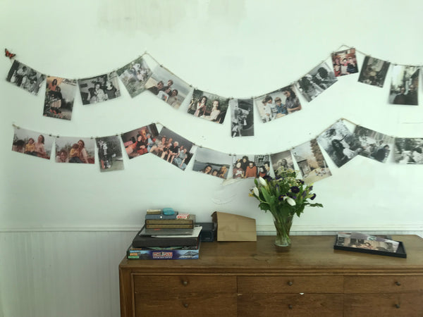 Binder clips pinning photos to twine