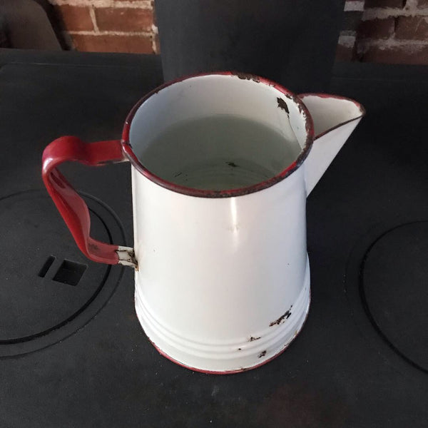 Antique enamel pitcher used as humidifier on wood stove
