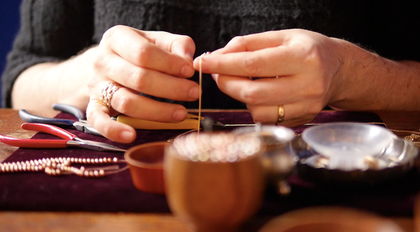 close up of hands making jewelry
