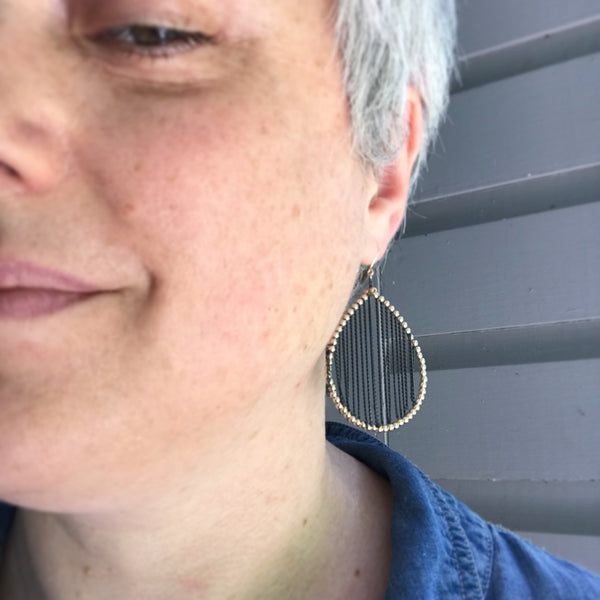 Model wearing gold and oxidized silver earrings