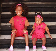 Two toddler sisters in pink and brown strip free romper sitting on stairs