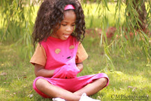 Toddler girl in pink and brown strip free romper sitting on grass