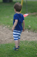 toddler boy in blue romper with white stripes on bottom back picture taken