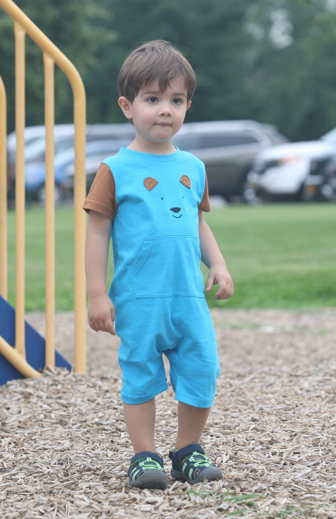 toddler boy in blue and brown romper with a bear head on front