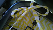 Fitted Crib Sheet with Ties -shows tied sheet ties around metal frame under the mattress in white with yellow chevron stripes