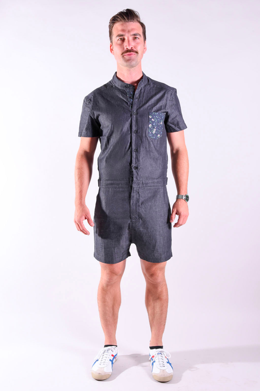 Lifestyle shot of model posing while wearing black chambray male romper by RompHim